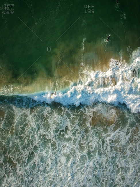 Aerial view of surfers and big wave in the ocean. Top view
