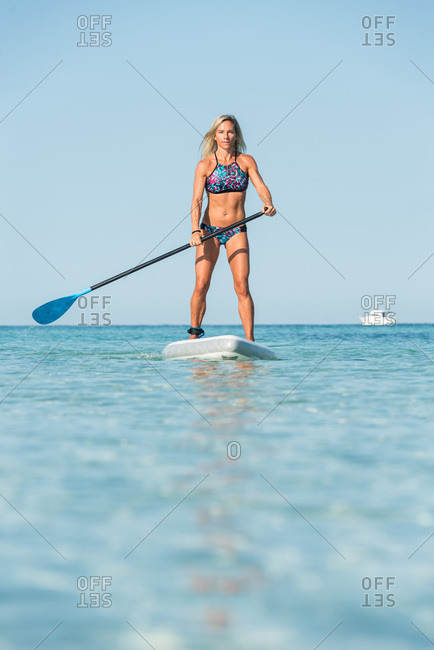 Fit female surfer in bikini standing on paddleboard and rowing while training in sea on sunny day