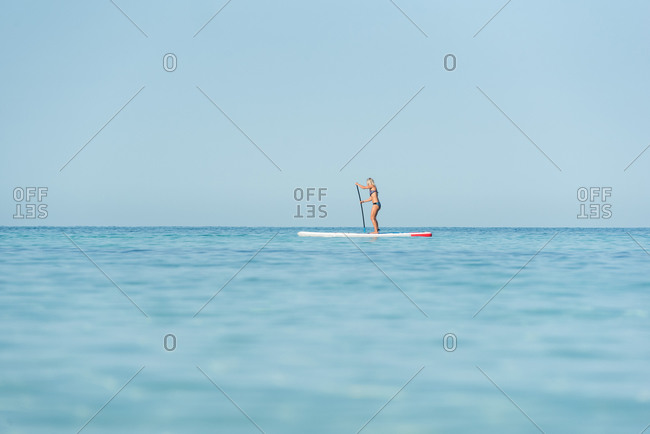 Side view of fit female surfer in bikini standing on paddleboard and rowing while training in sea on sunny day