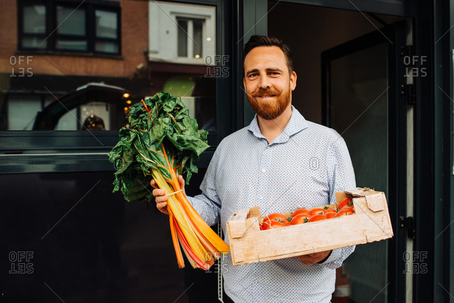 Delivery man holding box of tomatoes and greens at restaurant entrance