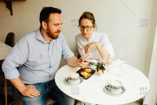 Heterosexual couple in cafe looking at smartphone and drinking coffee