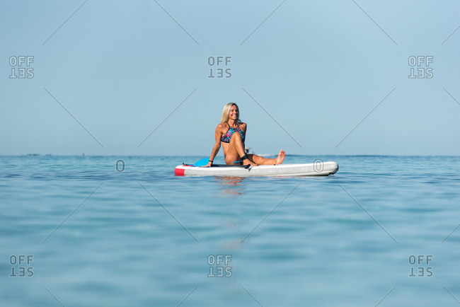 Fit happy female surfer sitting on surfboard with paddle and relaxing during training in calm sea in summer
