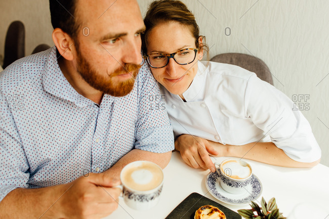 Couple drinking cappuccino while sitting at table in cafe