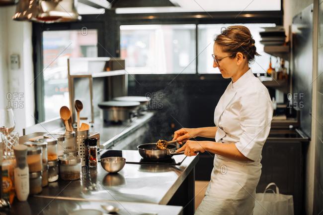 Female chef stirring hot food while working in restaurant kitchen