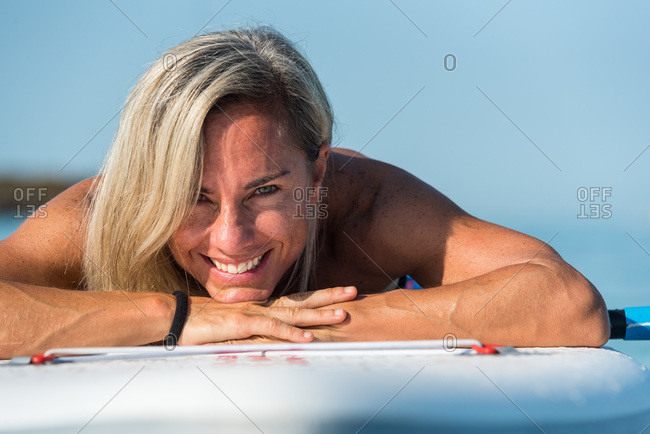Content female surfer lying on surfboard with paddle and resting during training on calm sea water while looking at camera
