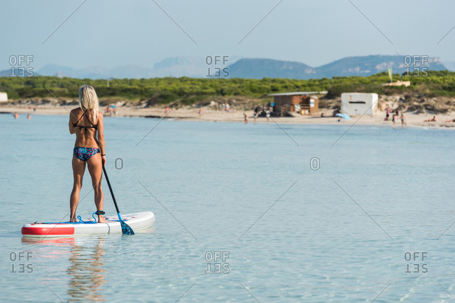 Back view of slender female in bikini standing on paddleboard and rowing on calm sea surface during training
