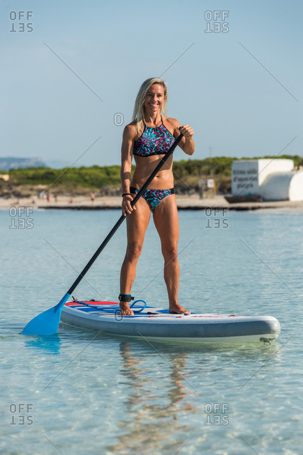 Slender fit female in bikini standing on paddleboard and rowing on calm sea surface during training