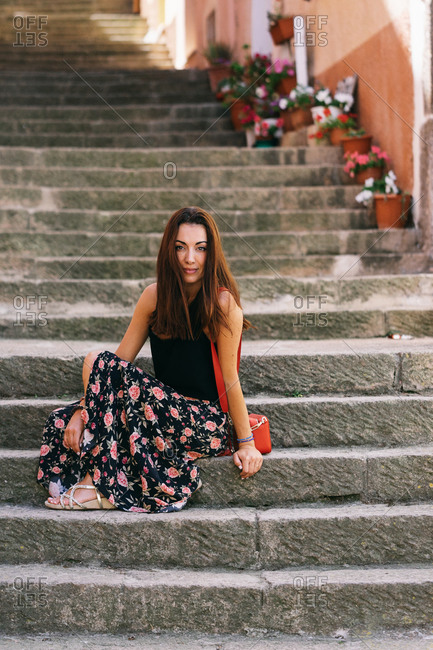 Delighted female tourist sitting on stairs in city and looking at camera during summer vacation
