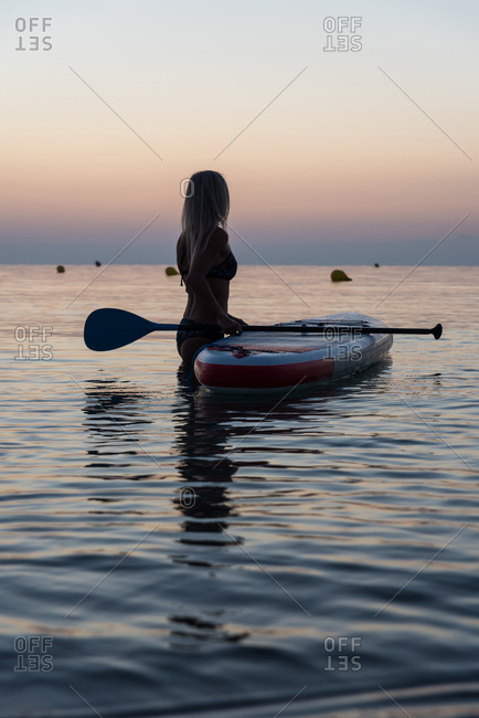 Side view of unrecognizable female surfer standing near paddleboard and rowing against spectacular sun in sunset sky