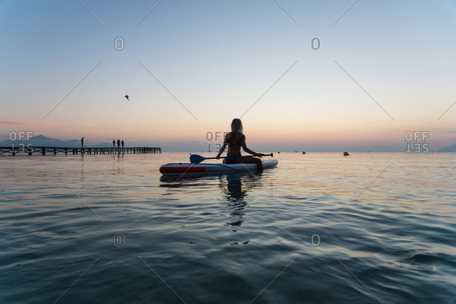 Back view of unrecognizable female surfer sitting on paddleboard and rowing against spectacular sun in sunset sky