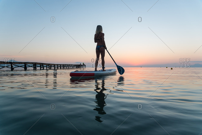 Back view of silhouette of unrecognizable female surfer standing on paddleboard and rowing against spectacular sun in sunset sky