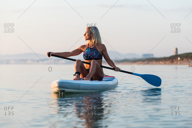 Side view of fit female surfer sitting on paddleboard and rowing against spectacular sun in sunset sky