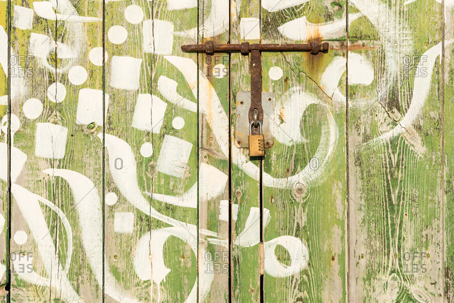 Old colorful wooden door with paintings and metal bolts lit by sunlight in Sa Caleta