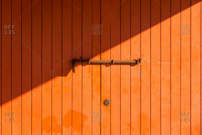 Weathered wooden colorful door with rusty metal bolt on sunny day in Sa Caleta