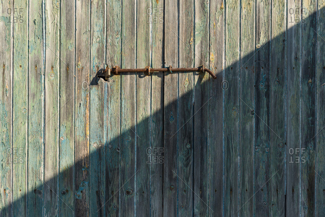 Weathered wooden door with rusty metal bolt on sunny day in Sa Caleta