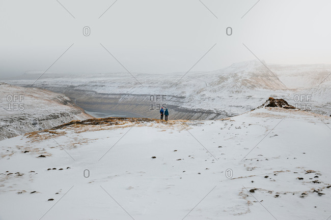 Back view of unrecognizable people admiring spectacular scenery of river surrounded by mountain range covered with snow in winter on overcast day on Faroe Islands