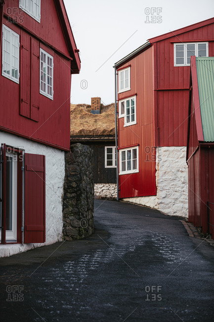 Narrow street with red wooden cottages located on Faroe Islands under cloudy sky in autumn