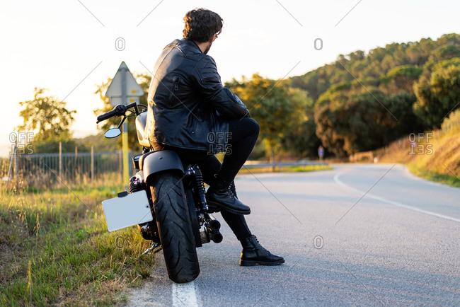 Rear view of bearded man sitting on a motorbike