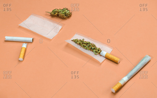 Steps and materials to roll a marijuana joint on orange background.