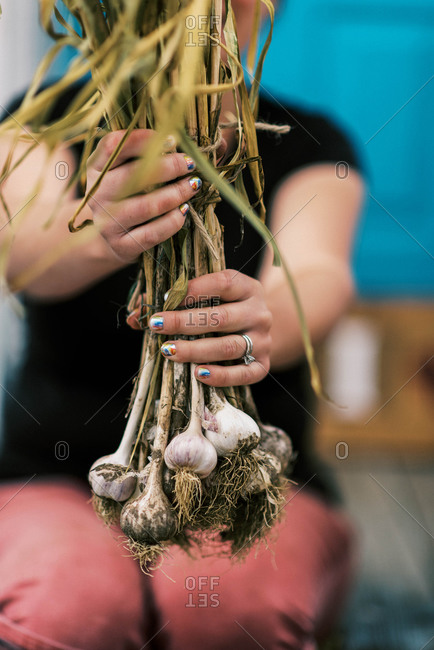 A woman holding up a bundle of cured garlic