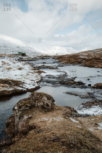 Spectacular scenery of river surrounded by mountain range covered with snow in winter on overcast day on Faroe Islands