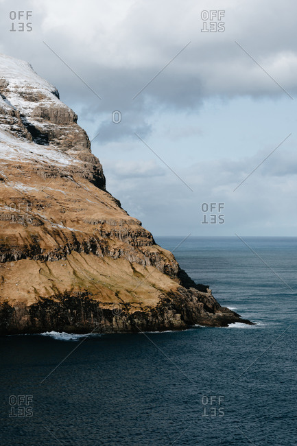 Majestic scenery of rocky terrain covered with snow near calm sea on cloudy day on Faroe Islands
