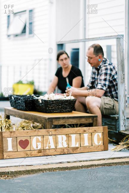 Two urban farmers sitting on their porch while processing their garlic
