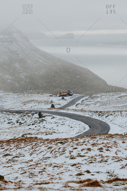 Empty asphalt road covered with snow and surrounded by mountains on cloudy day on Faroe Islands