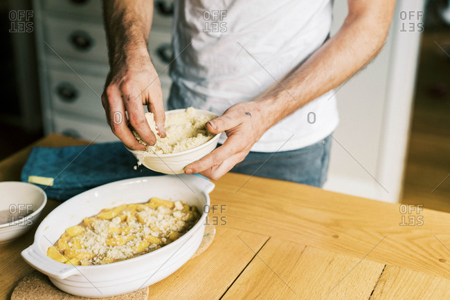 A father putting streusel on a peach cobbler