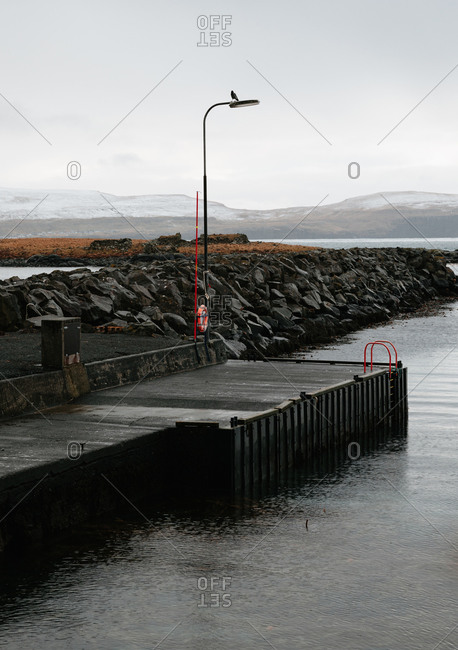 Detail of wet wooden quay located near calm sea on overcast day on background of mountain range on Faroe Islands