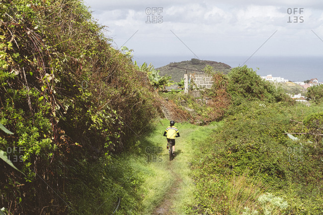 back view of female cyclist riding on grassy path