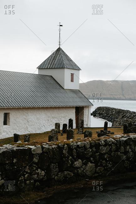 Small village church located near local cemetery near river against gray overcast sky in winter day in the Faroe island