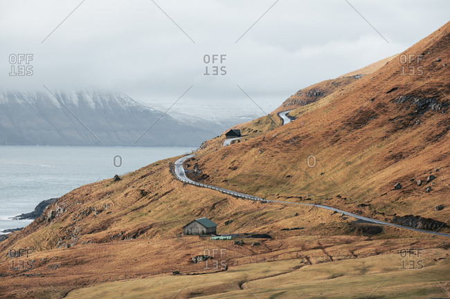 Narrow countryside road and small cottage located on coast of calm sea on cloudy day on Faroe Islands