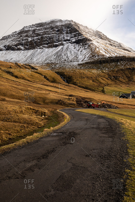 Wooden residential house in settlement in autumn on Faroe Islands on snowy mountains