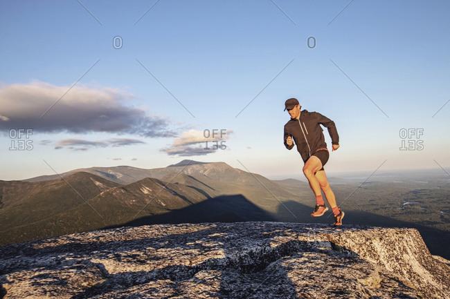 Fit male trail runner runs across rocks on summit of Doubletop, Maine