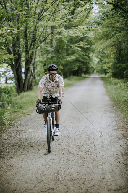 Male cyclist rides gravel section of East Coast Greenway, Maine