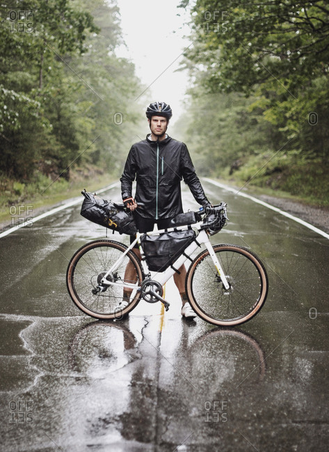 Male bike packer stands with bike in road in pouring rain, Maine
