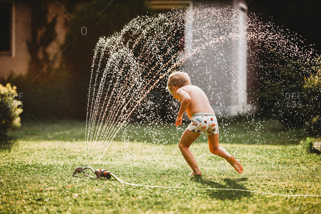 Young white boy running under the water from the sprinkler in garden
