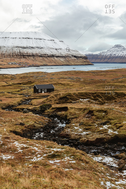 Breathtaking scenery of residential wooden house located near river in highland valley with mountains covered with snow on Faroe Islands