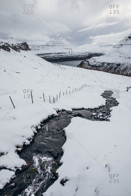 Narrow creek with cold water flowing under snow against mountains and overcast sky on Faroe Island