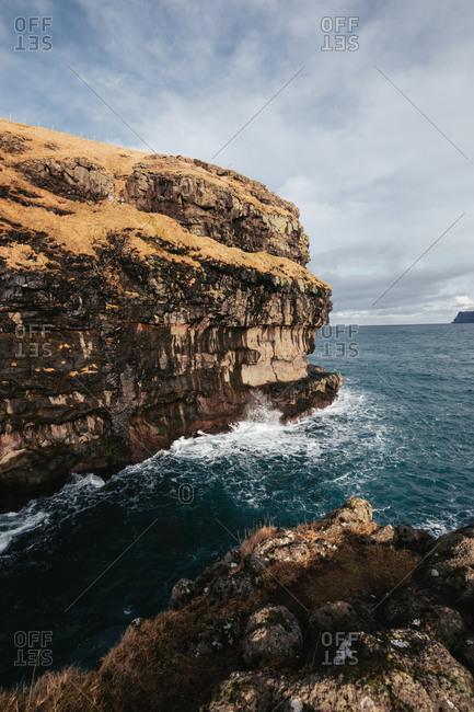 Majestic scenery of rocky terrain near calm sea on cloudy day on Faroe Islands