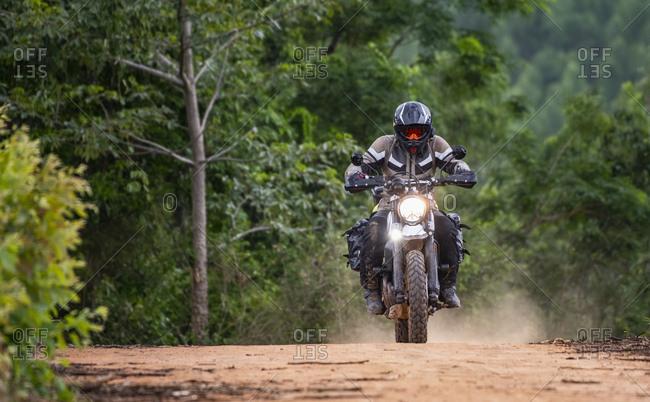 Man riding his motorbike on gravel road in Pak Chong / Thailand