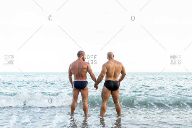 Back view of muscular gay couple holding hands and looking to the seascape.