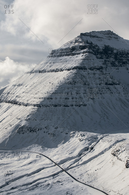 Picturesque view of mountainous terrain covered with white snow against gray sky on cold winter day in Faroe Iceland in Iceland