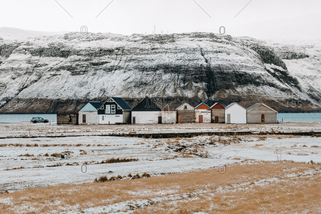 Breathtaking scenery of residential houses located near river in highland valley with mountains covered with snow on Faroe Islands