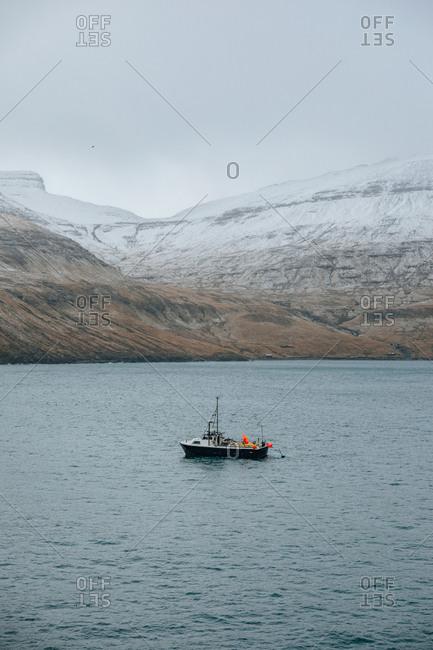 Fish boat on the sea near snowy mountain range during winter on faroe island