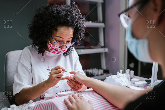Ethnic female artist applying nail polish on fingernails of client during manicure in beauty studio