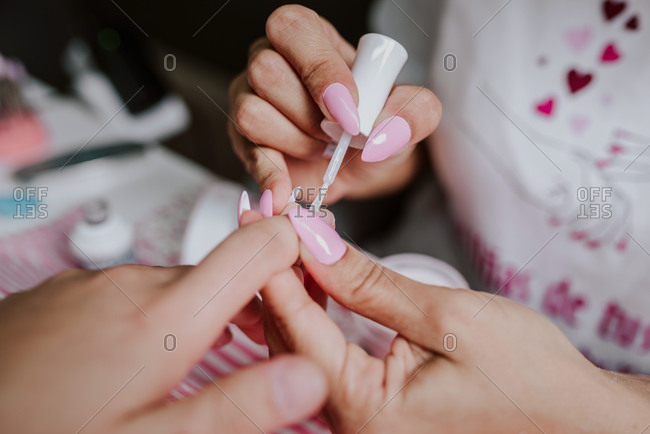 High angle of unrecognizable female artist applying nail polish on fingernails of client during manicure in beauty studio