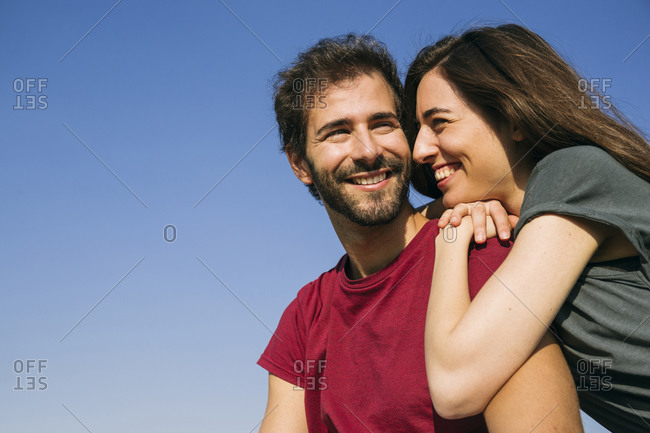 Young woman leaning on man shoulder against clear sky