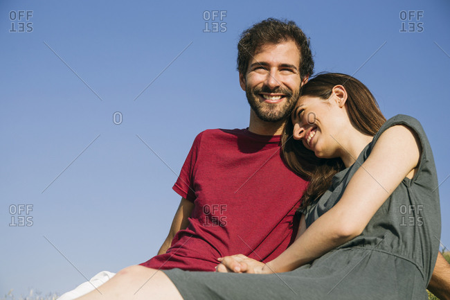 Woman smiling while leaning on man's shoulder against clear sky